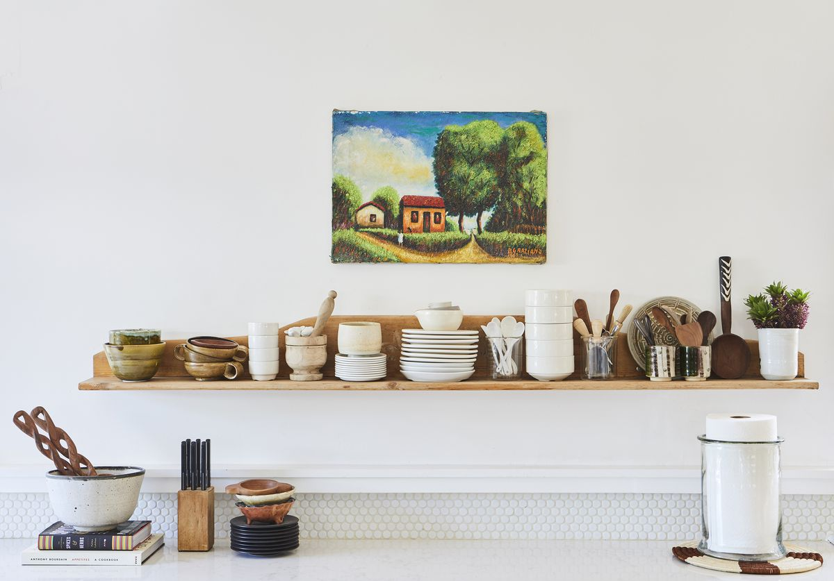 A natural wood shelf makes for open shelving in the white kitchen.
