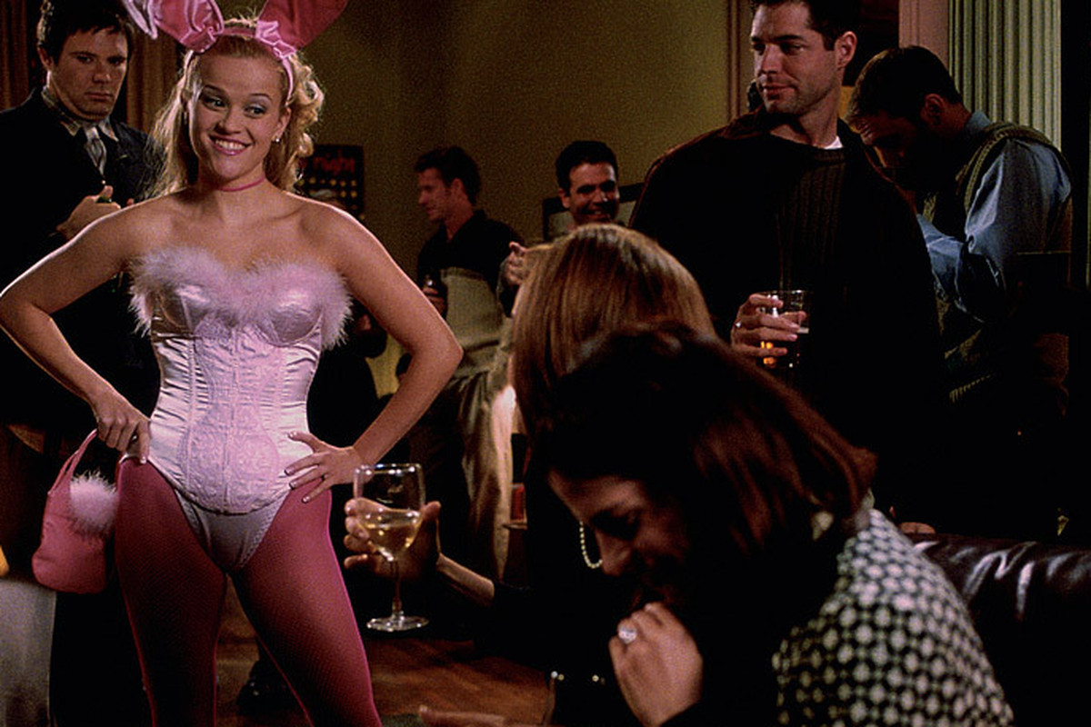 Elle Woods stands in a bunny suit next to laughing girls
