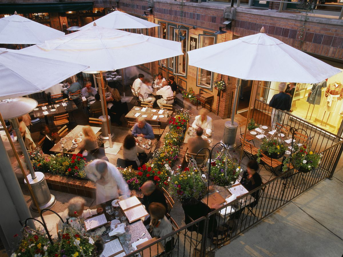 From above, a patio seating area, with tables full of people, servers moving about, and white umbrellas