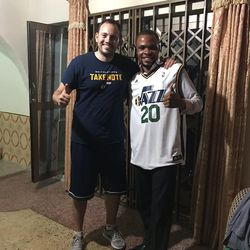 Ghanaian Dennis Agyekum, an Abomosu coach, teacher and sports director, is all smiles in his white Gordon Hayward jersey that was given to him by Zach Harding after being donated.