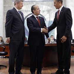 Canada's Prime Minister Stephen Harper, left, looks on as President Barack Obama, and Mexico's President Felipe Calderon, center, shake hands during the North American Leaders Summit in Guadalajara, Mexico, Monday.