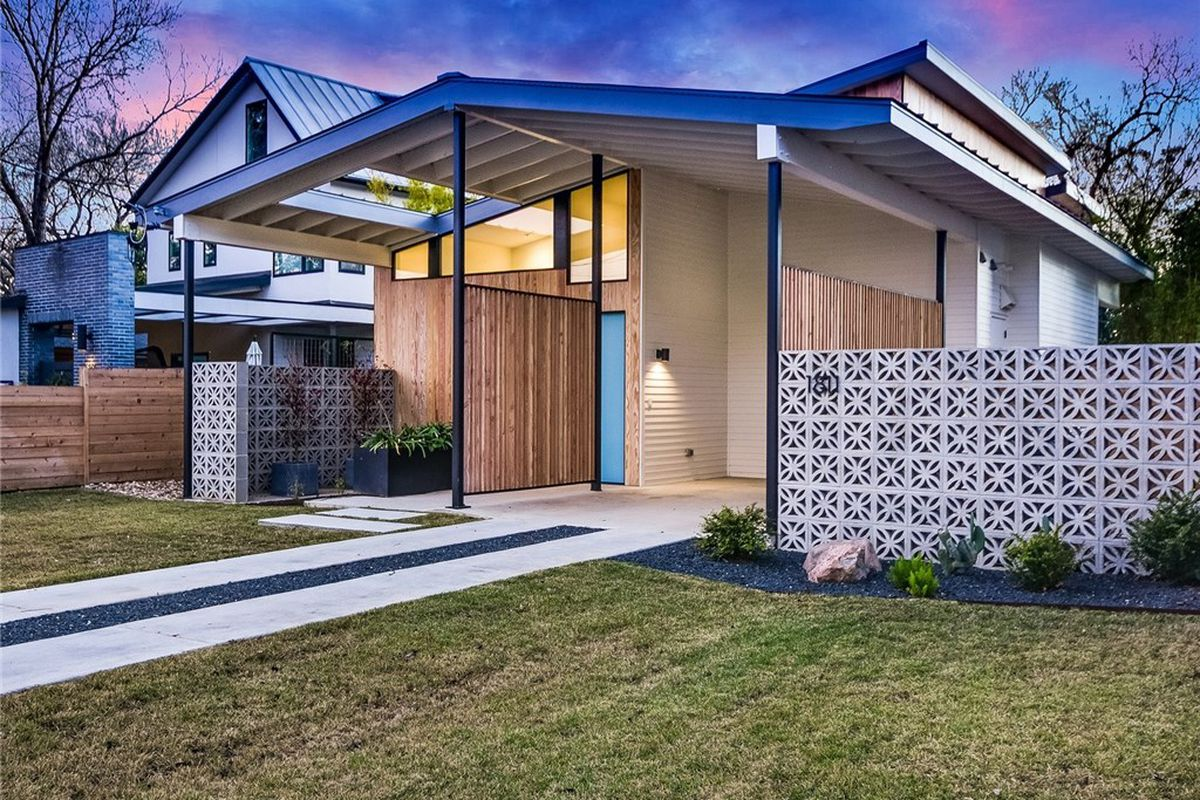 Exterior dusk photo of a contemporary one-story home with midcentury-style features such as breezeblock fence and a modified butterfly roof.