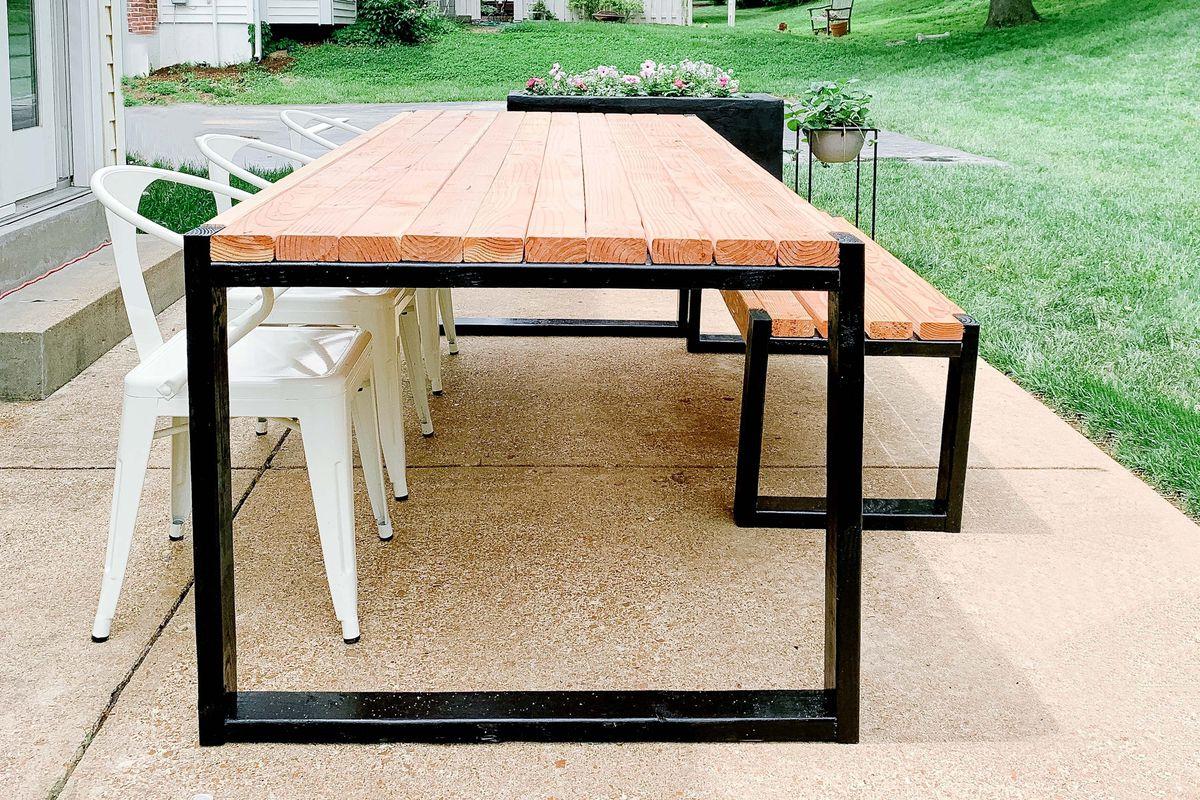 A handmade DIY table sits on a back patio.