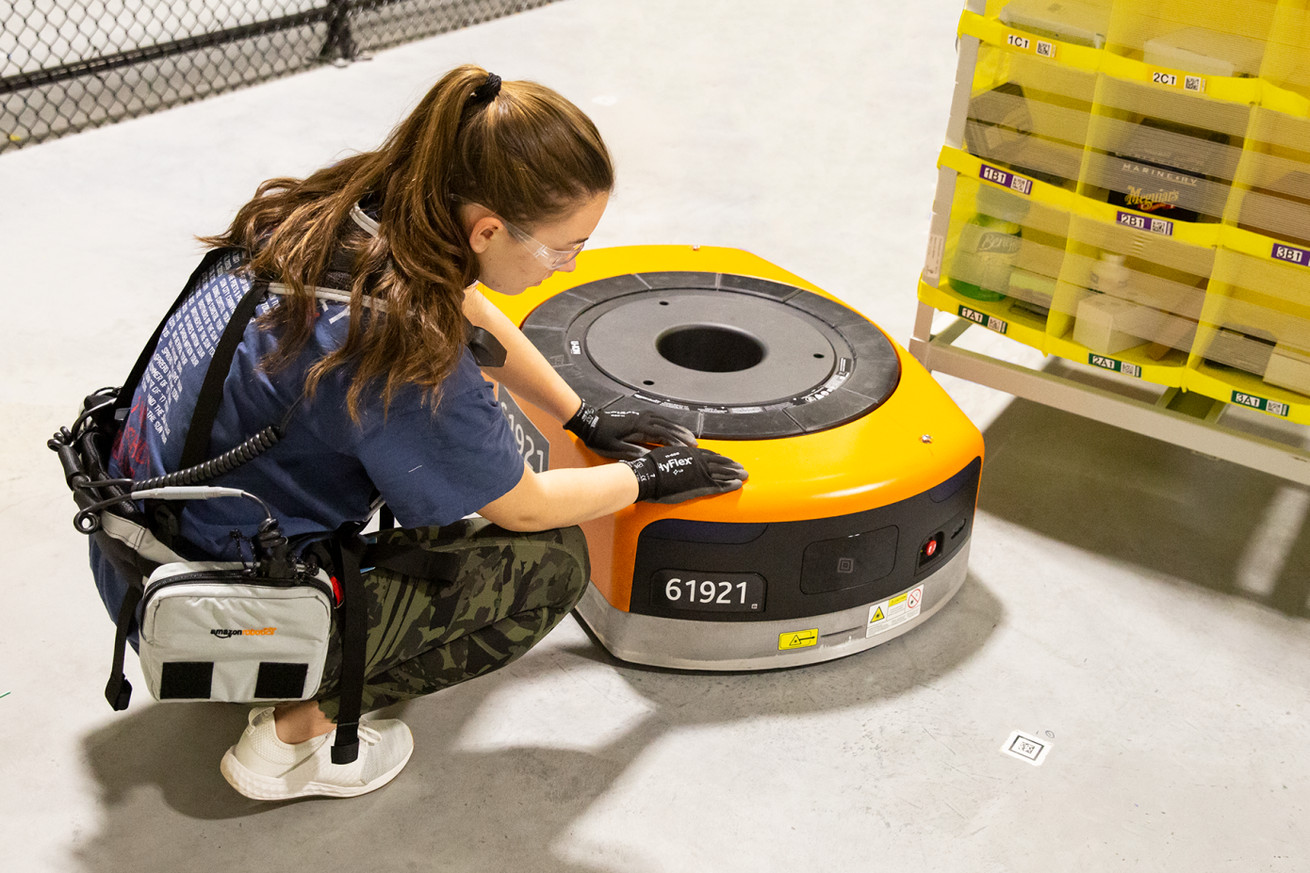 An Amazon employee wearing the Robotic Tech Vest inspects a warehouse robot.