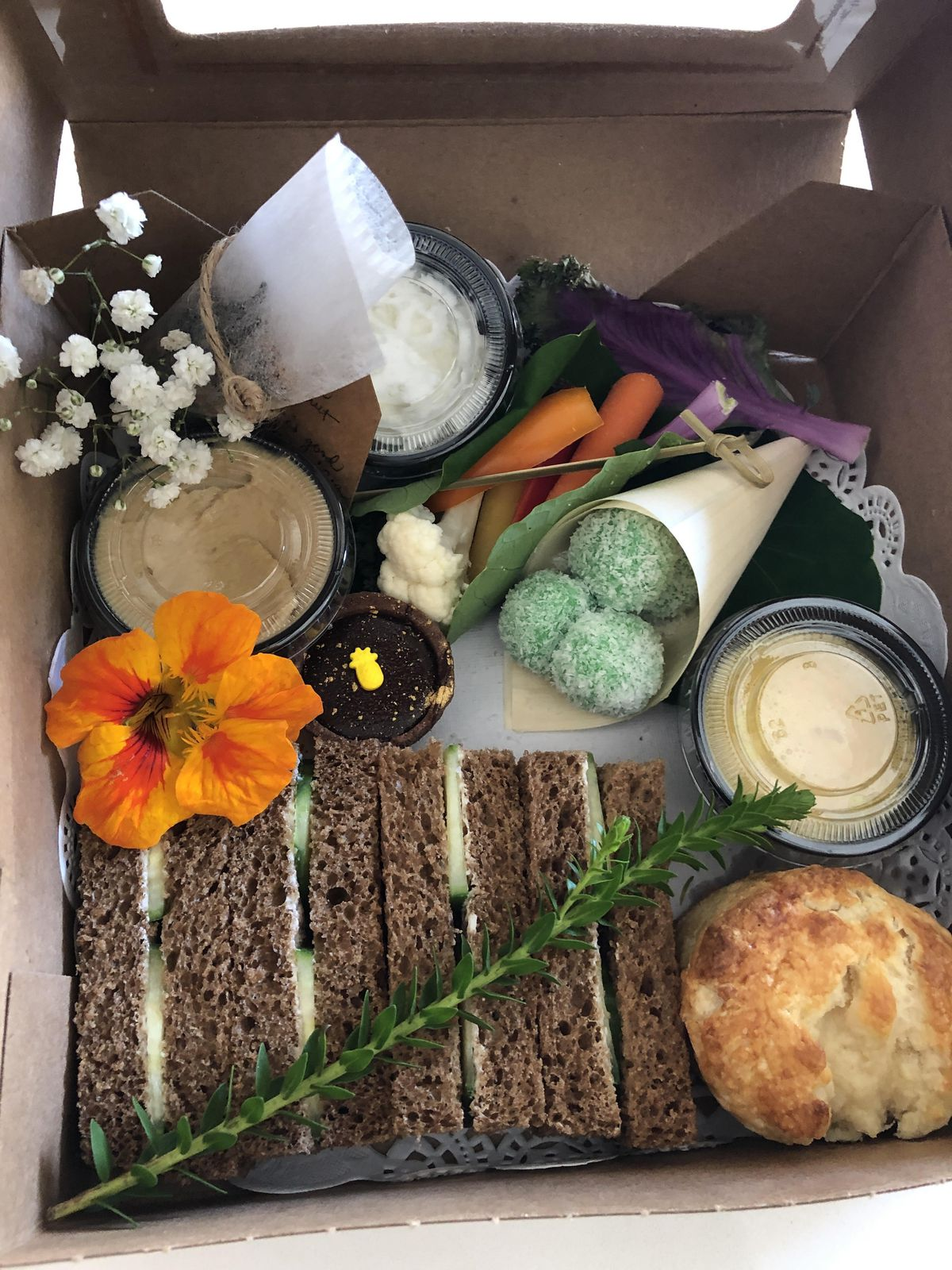 Close-up of another afternoon tea box, with finger sandwiches, scones, and a garnish of fresh flowers