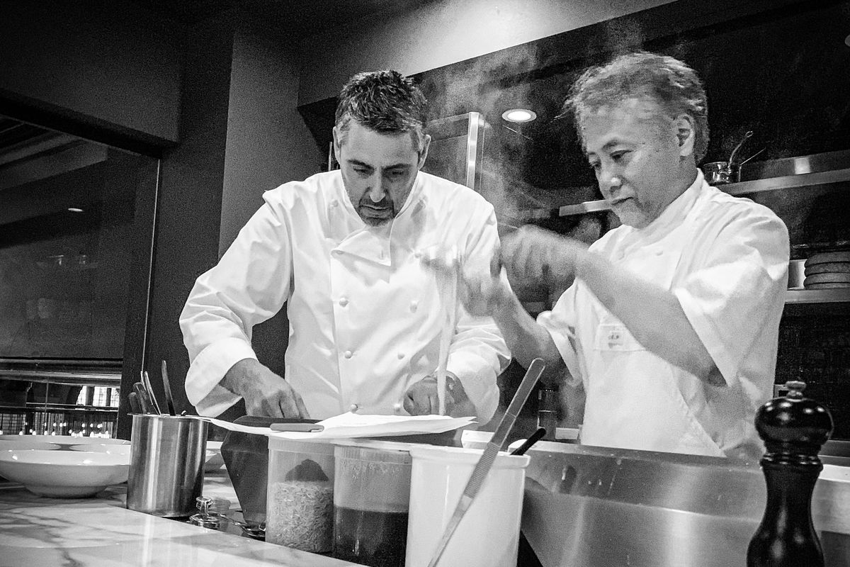 A black and white photo of chef Luciano DelSignore and chef Takashi Yagihashi standing in a kitchen in front of a steaming pot and a marble counter wearing white chefs coats.