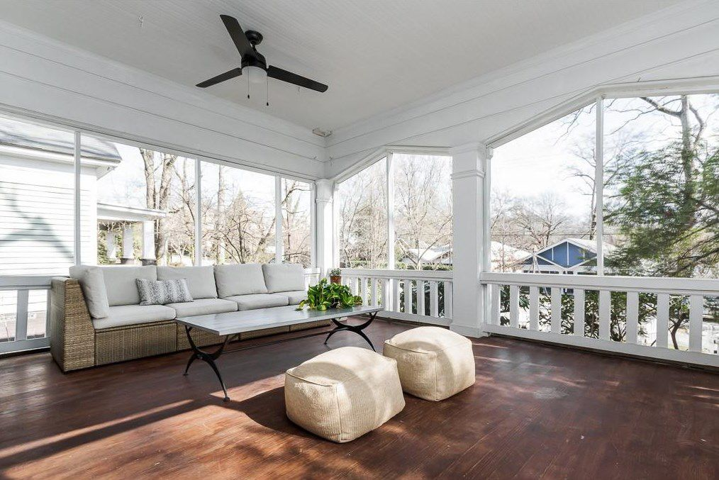 A white front porch with a brown ceiling fan.
