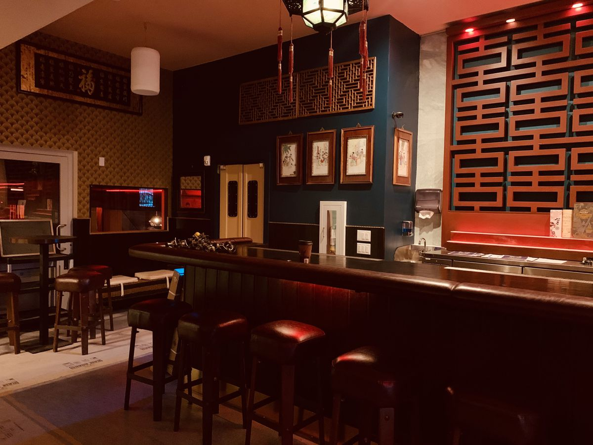 View of a dark wood bar with leather elbow rests and vintage bar stools