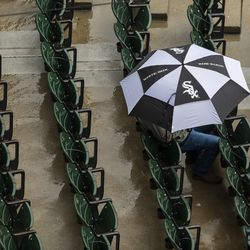 A Chicago White Sox fan waits for the home opener to begin while sitting under an umbrella, at Guaranteed Rate Field, Thursday, April 8, 2021.