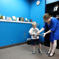 Fire Petal Books owner Michelle Witte shows Bridger Nielsen, 6, a book at her new bookstore.