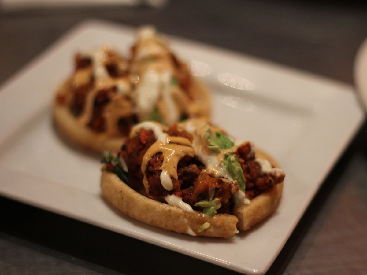 A close-up on sopes topped with chorizo and abalone, and drizzled with various sauces