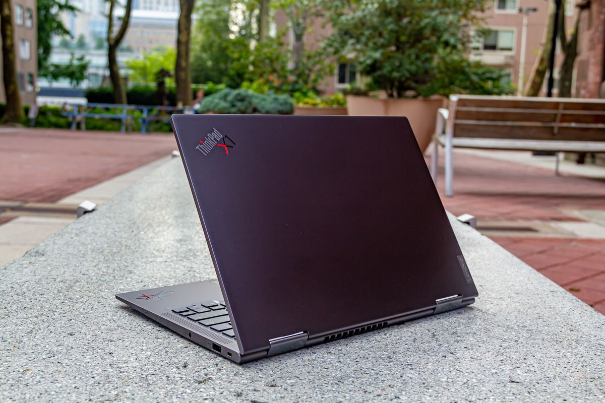 The ThinkPd X1 Yoga Gen 6 half open, angled to the left, seen from behind on a stone bench outdoors.