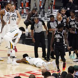 Utah Jazz guard Donovan Mitchell, below, lays on the ground after being injured as members of the Jazz and Los Angeles Clippers stand by during the second half in Game 6 of a second-round NBA basketball playoff series Friday, June 18, 2021, in Los Angeles.