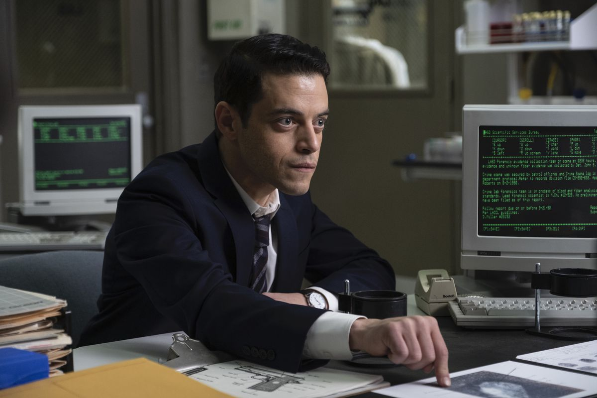 Rami Malek in a suit sits at a desk with old '90s computers and points his finger down like he means it in The Little Things
