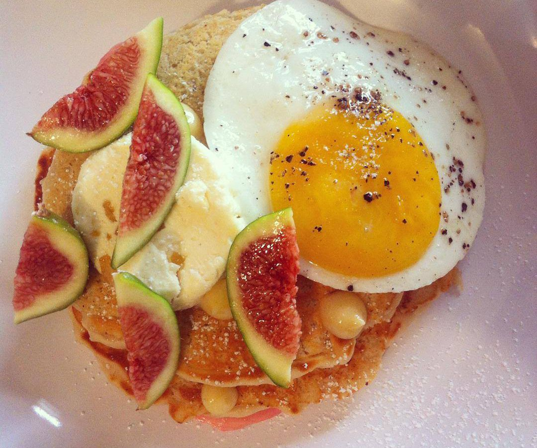 From above, a plate of hotcakes topped with slices of fig and a sunny-side-up egg