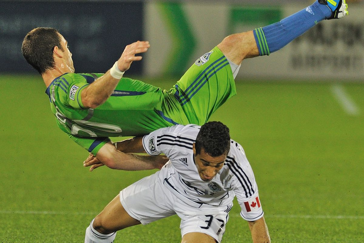 VANCOUVER, CANADA - SEPTEMBER 24: Amadou Sanyang #30 of the Seattle Sounders falls over Camilo Sanvezzo #37 of the Vancouver Whitecaps during their game at Empire Stadium September 24, 2011 in Vancouver, Canada.   (Photo by Nick Didlick/Getty Images)