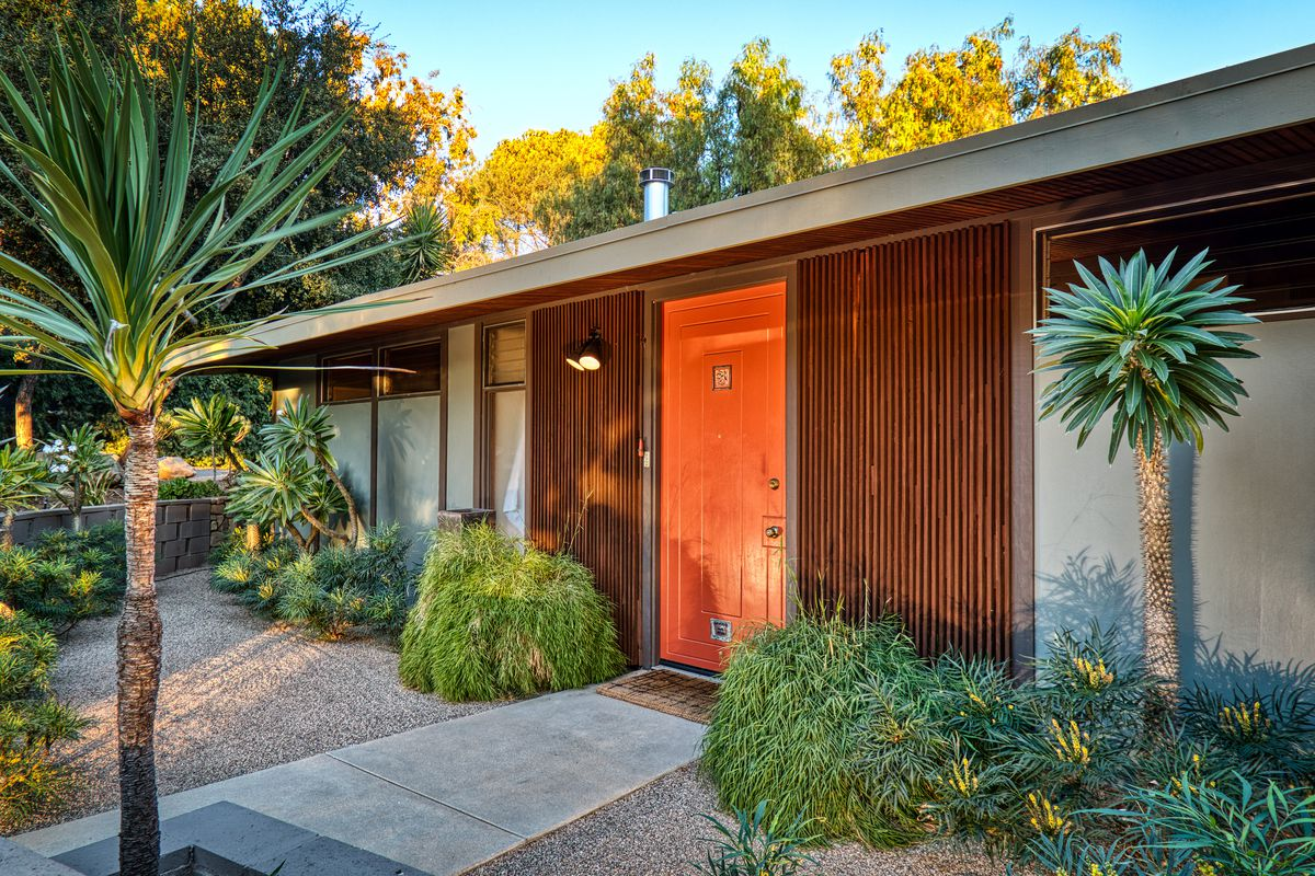 An exterior view of a flat-roofed midcentury house with a bright orange door and desert-style landscaping around it.