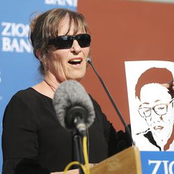 """Artist Jann Haworth holds a cutout ofJennifer Nii as she talks about her """"Utah Women 2020"""" mural on the Dinwoodey Building in Salt Lake City during its unveiling on Wednesday, Aug. 26, 2020.The mural, commissioned by Zions Bank in honor of women's suffrage, depicts images of 250 Utah women past and present, including Nii."""