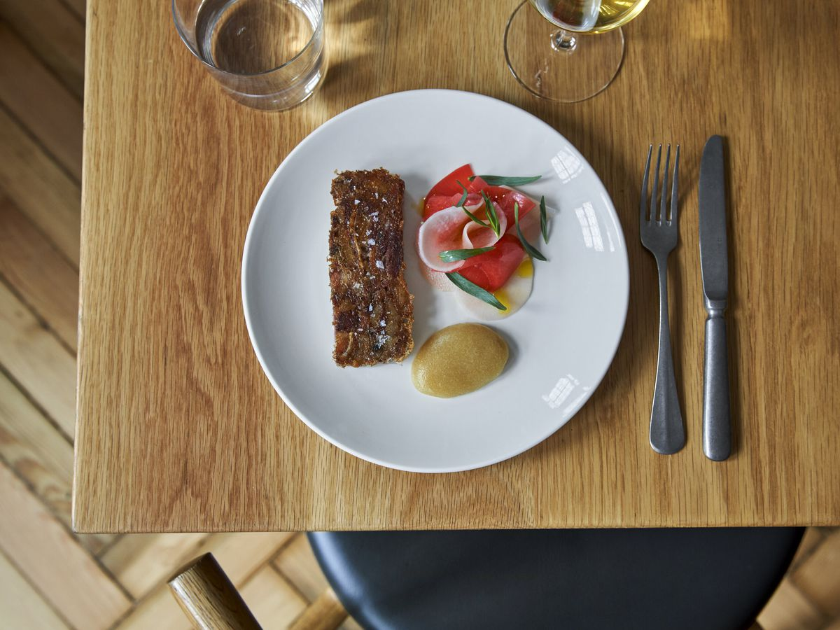 Pressed pig's head with apple sauce and pickled radish, red and white, on a white plate