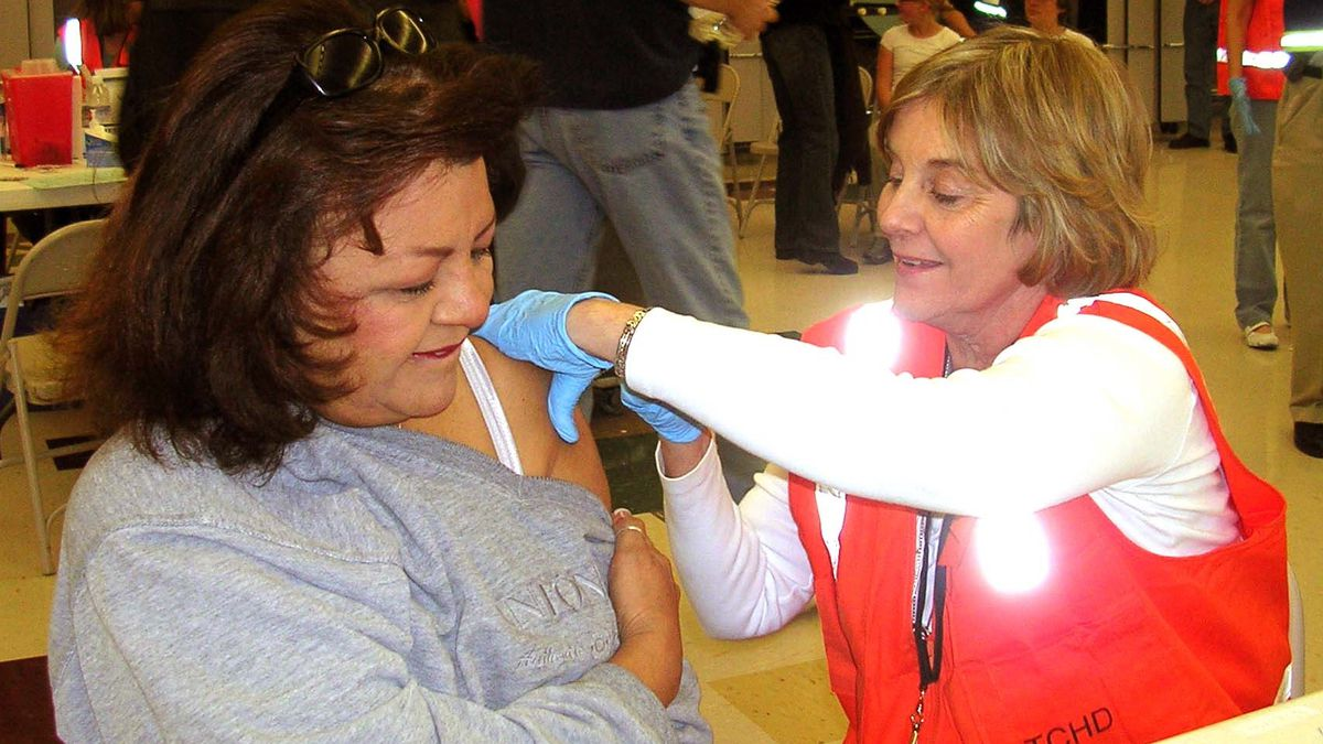 A school nurse in Douglas County gives a shot at a school flu clinic, another nursing task.