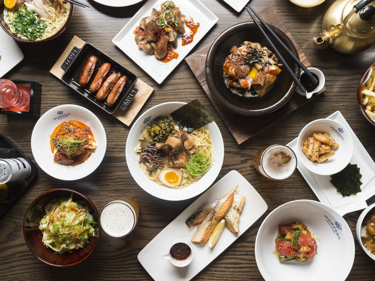Overhead view of a table full of Japanese dishes, including ramen and lots more