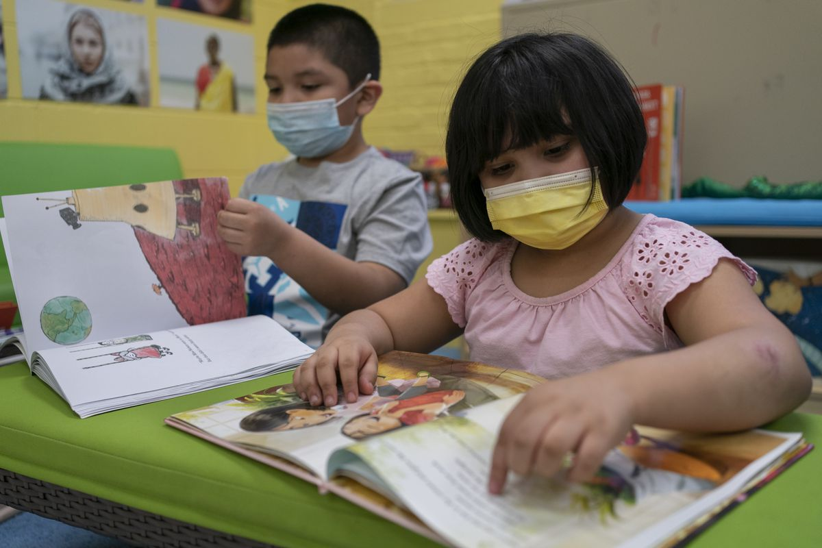 A young boy wearing a blue face mask and a gray shirt looks at a book. Next to him a young girl with a yellow face mask and a pink shirt looks at another book. Both are at a lime green desk or table.