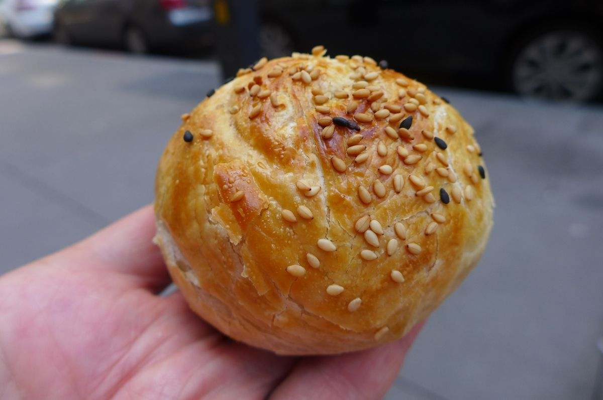A round turnover topped with seeds is held in a hand.