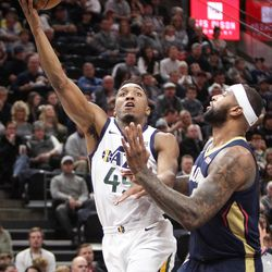 Utah Jazz guard Donovan Mitchell (45) lays the ball up over New Orleans Pelicans center DeMarcus Cousins (0) as Utah hosts New Orleans at Vivint Arena in Salt Lake on Friday, Dec. 1, 2017.