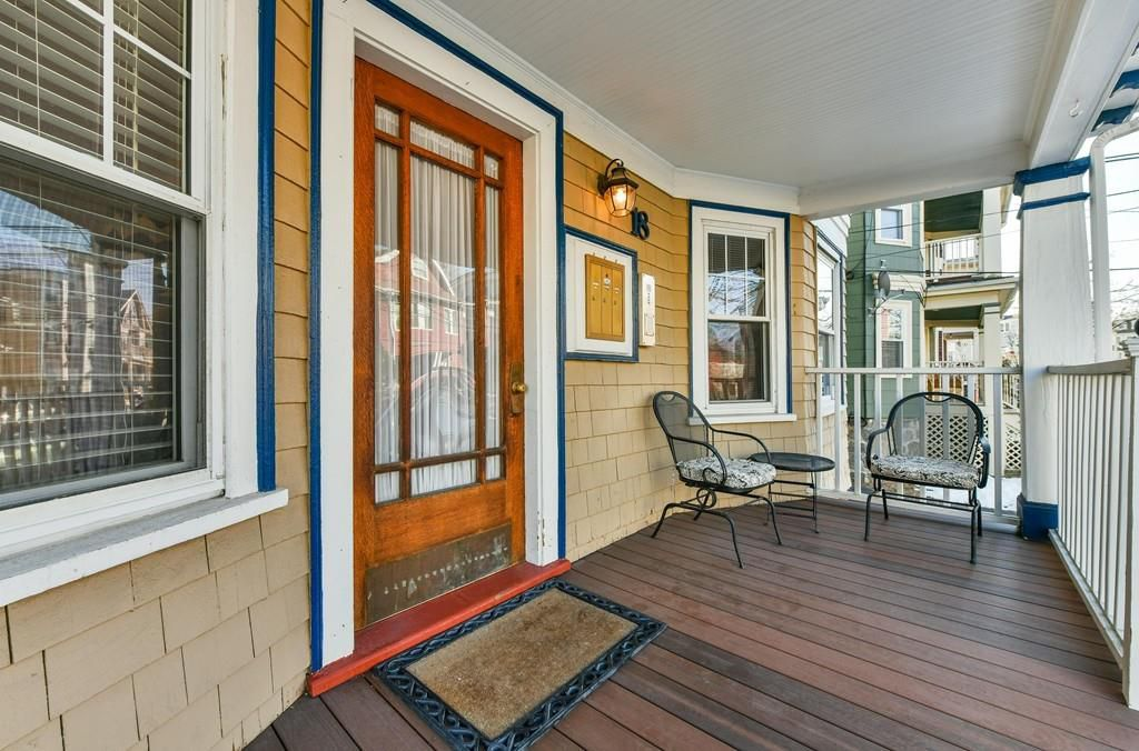 A front deck just outside of a closed front door, with two chairs at one end.