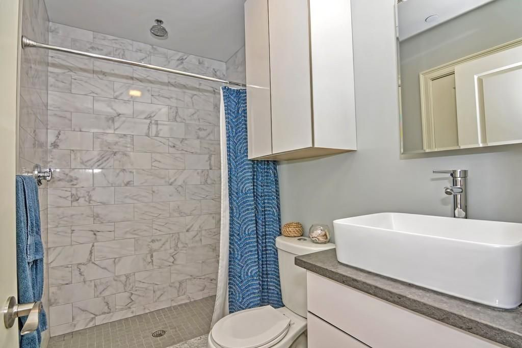 A bathroom with a basin sink and the curtain pulled back on the shower.