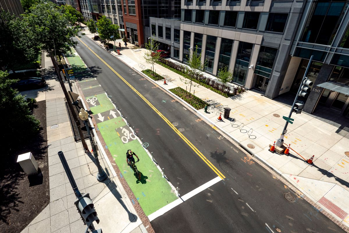 A city road that has a two-way bike lane and a couple of lanes for vehicular traffic.