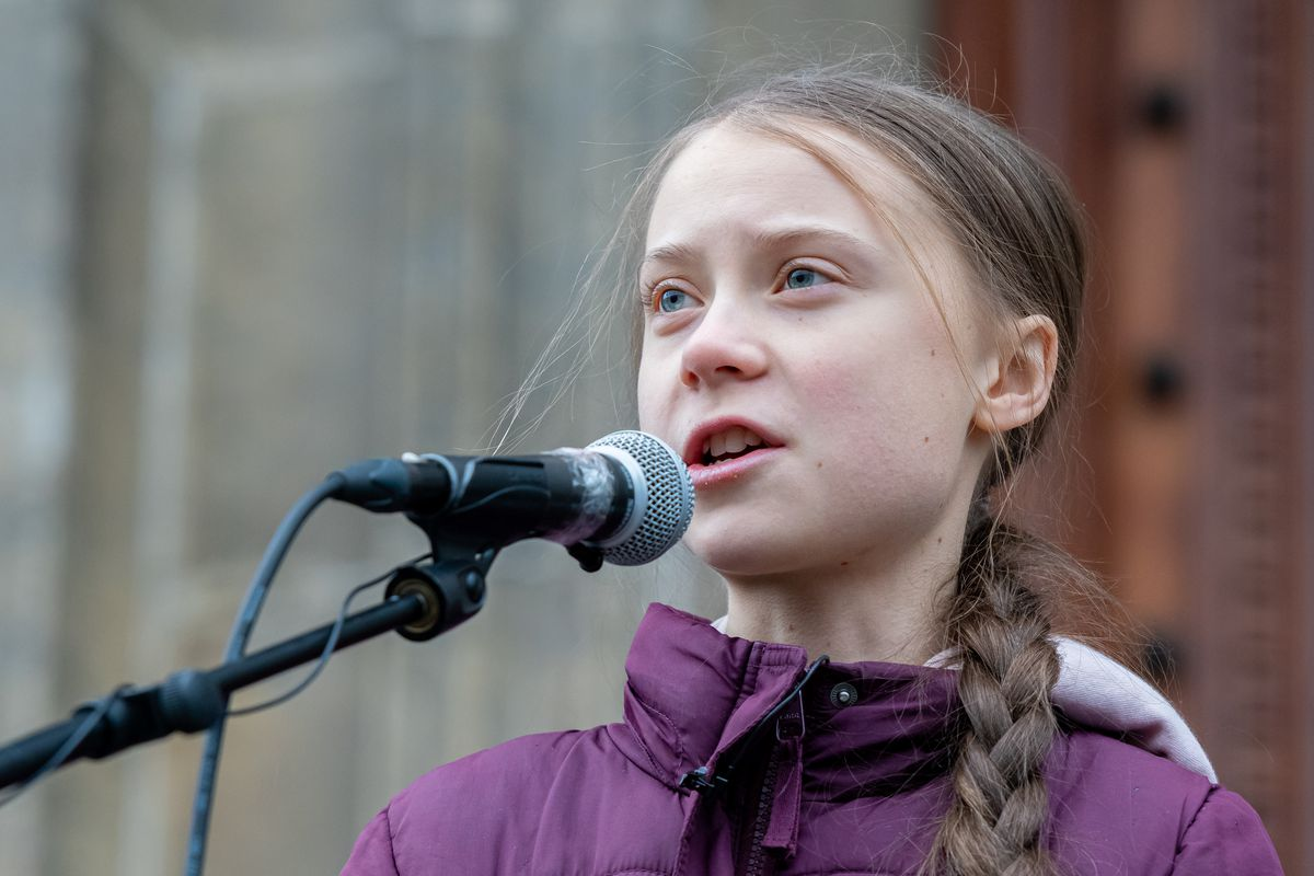 Greta Thunberg, wearing a purple jacket, speaks into a microphone.