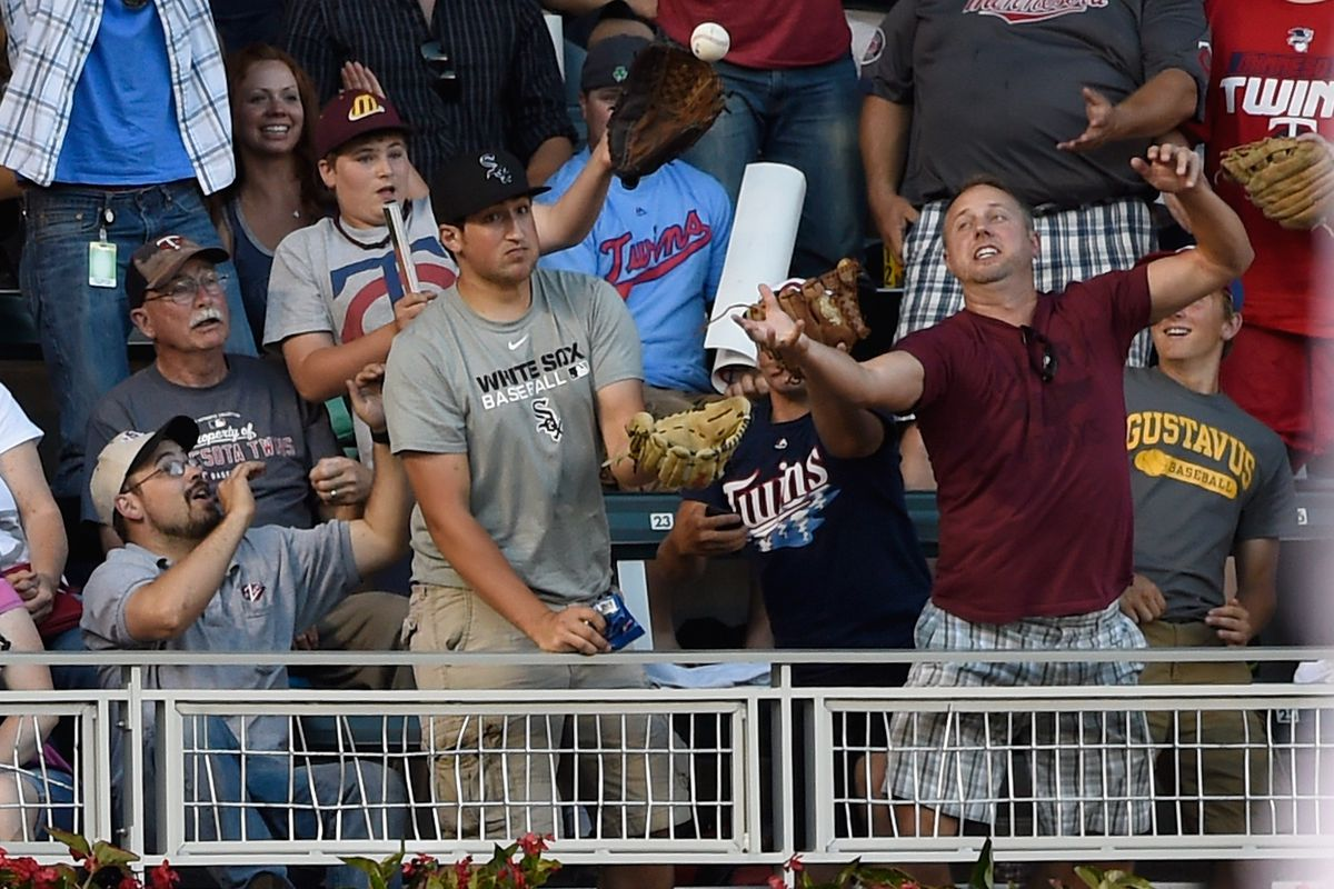 A Twins fan tries to catch a home run hit by Joe Mauer (seriously).