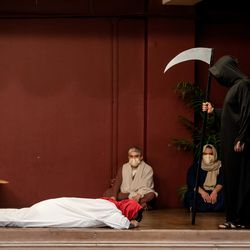 Isaac Bucio, who plays Jesus Christ, lies down on the stage as a man dressed as death faces him during Via Crucis in Pilsen, Friday morning, April 2, 2021. The annual Via Crucis is a Good Friday tradition that reenacts the Stations of the Cross, a Catholic devotion that recounts Jesus' passion and death.