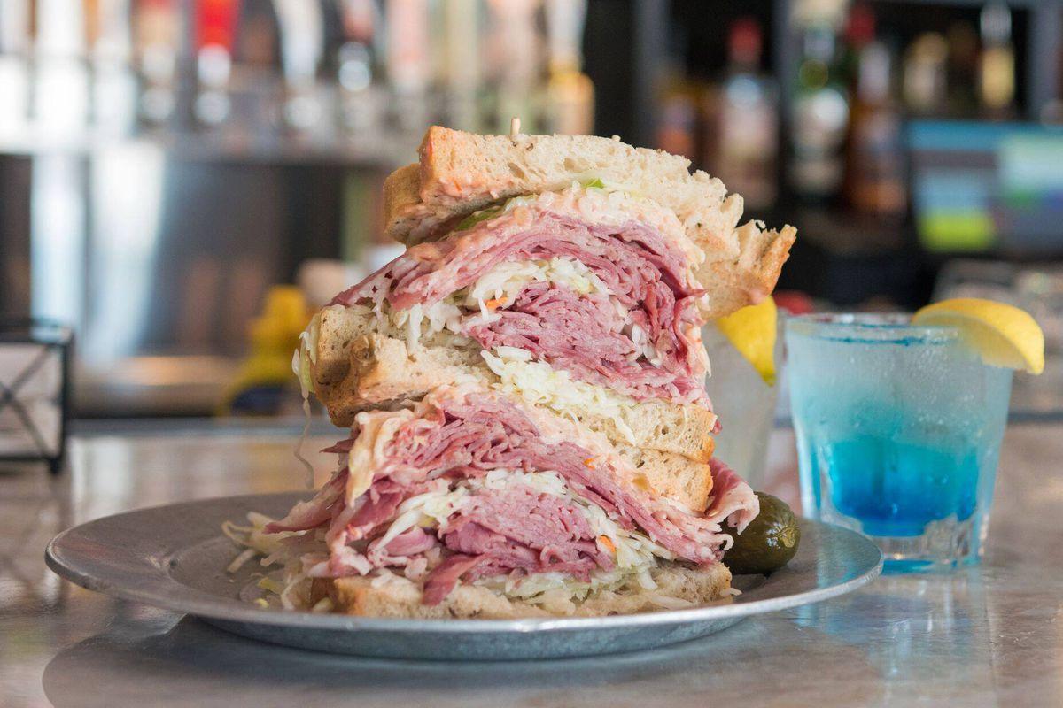 a double-decker reuban sandwich next to a neon blue cocktail.