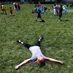 A student rests after running through a water cannon to celebrate the last day of school at Crestview Elementary in Holladay on Friday, May 27, 2016.
