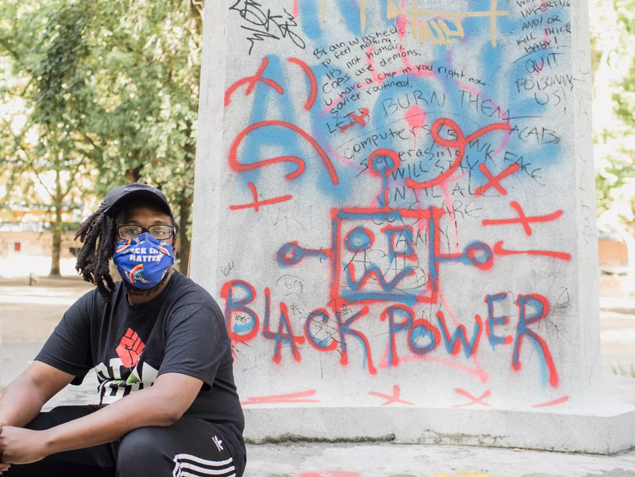 "A man in a mask sits in front of ""Black Power"" graffiti"