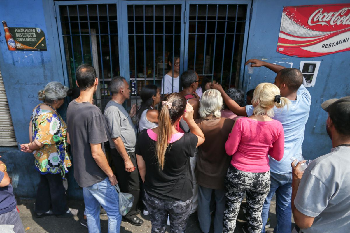 People queue outside a store to buy groceries in Caracas on March 8, 2019.