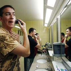At front, Elder Samuel Miller shaves on the morning of the day he is scheduled to leave the Provo Missionary Training Center of The Church of Jesus Christ of Latter-day Saints in Provo, Utah Tuesday, Feb. 15, 2011. In the background are Elders John Scoggin and Anthony Franklin.