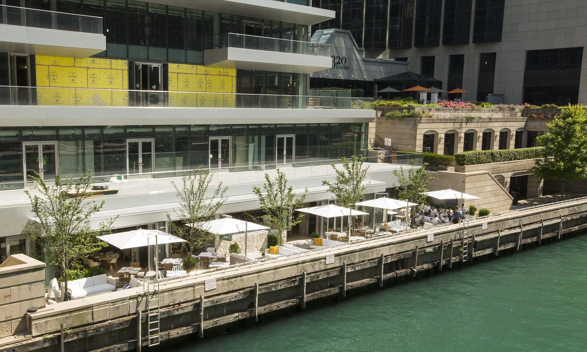 A cafe with white awnings along the Chicago River.