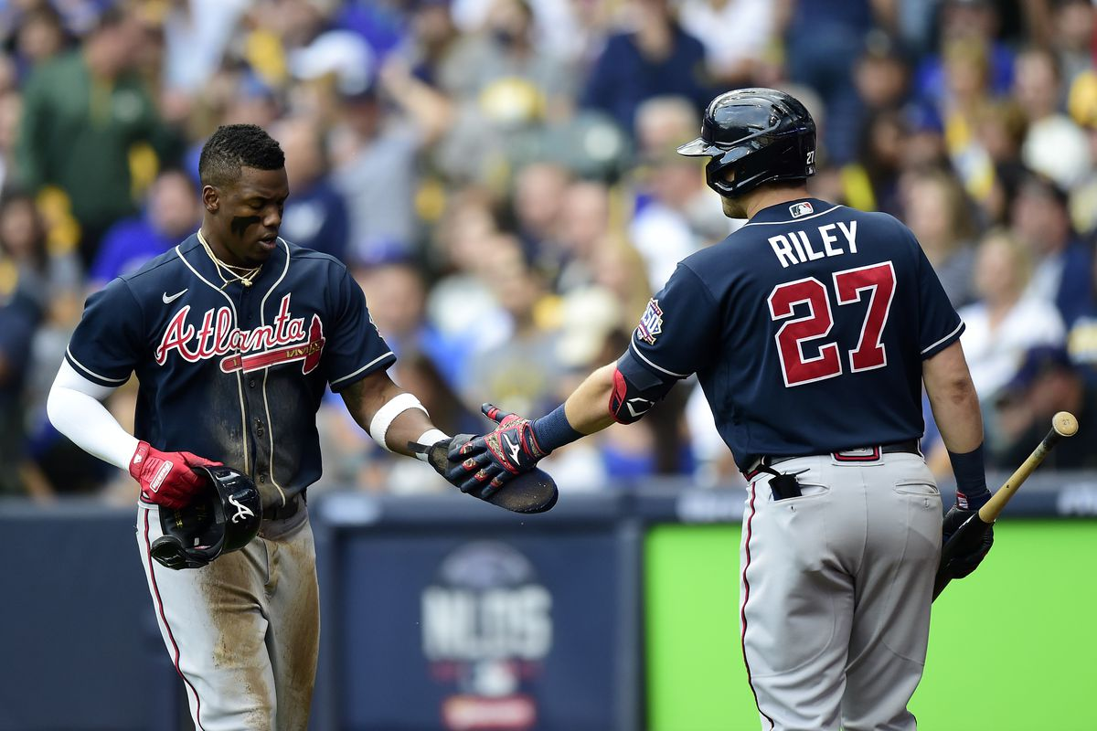 Jorge Soler #12 of the Atlanta Braves celebrates scoring a run with Austin Riley #27 of the Atlanta Braves in the third inning during game 2 of the National League Division Series against the Milwaukee Brewers at American Family Field on October 09, 2021 in Milwaukee, Wisconsin.