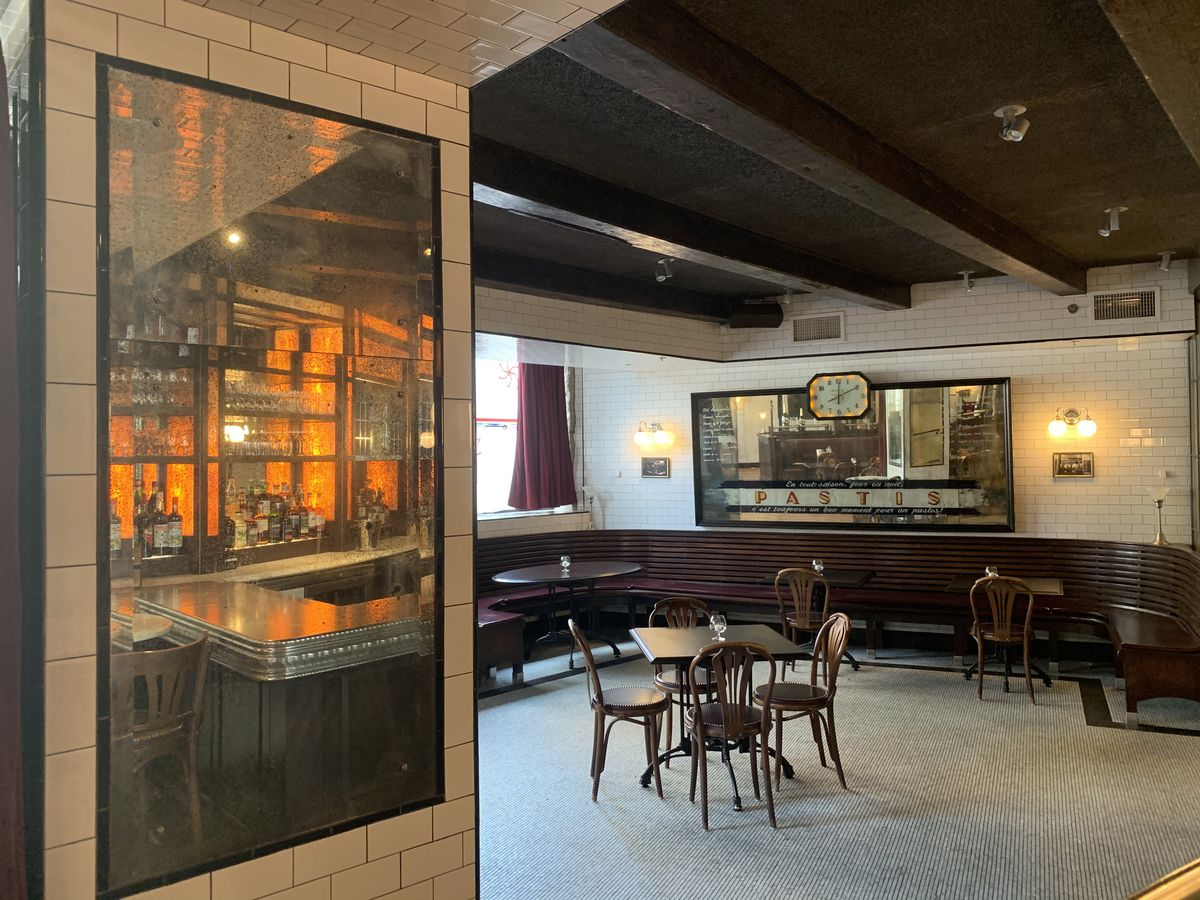 A French-inspired restaurant dining room, featuring white subway tile and dark exposed beams on the ceiling, features a large mirror that reflects a view of the bar