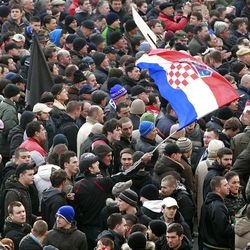 Protesters chant slogans and wave a Croatian flag during a protest in Zagreb, Croatia, Saturday, Feb. 26, 2011. Some 15,000 anti-government protesters rallied in the Croatian capital on Saturday, and state television reported that some clashed with police, who used tear gas to disperse them.