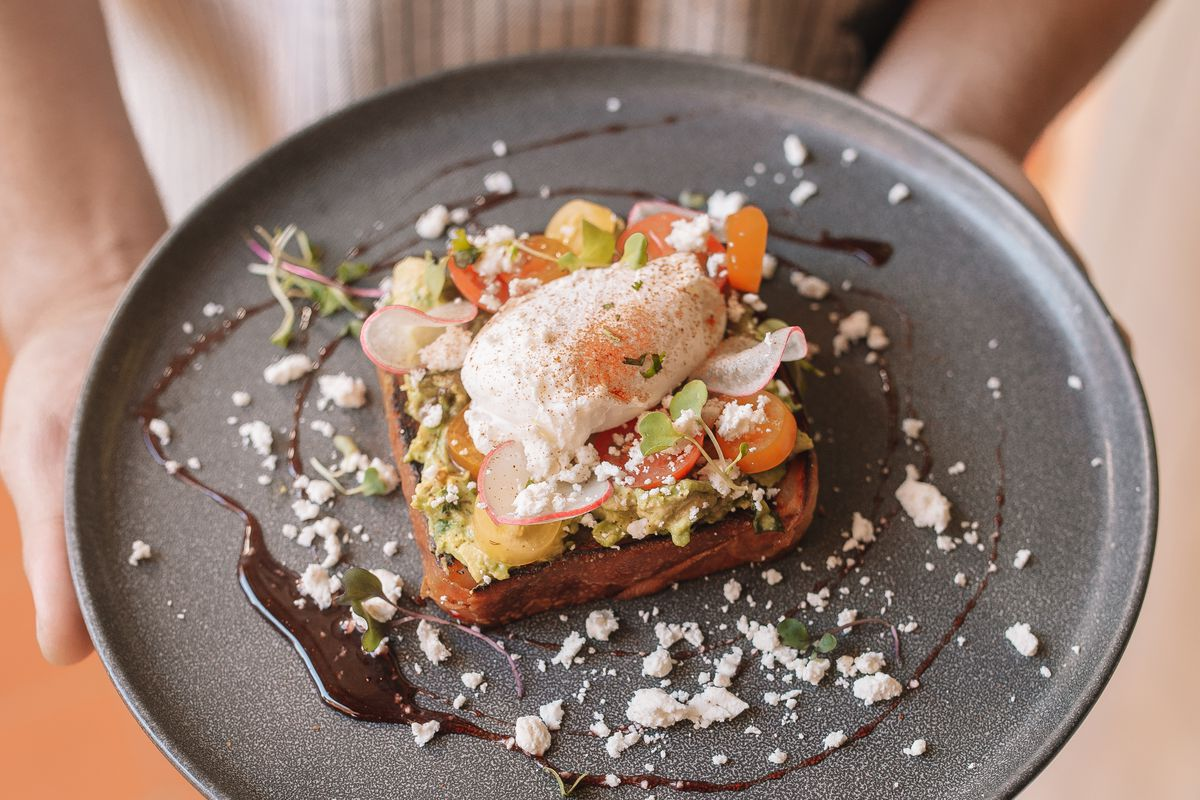 A man holds a plate with a piece of toast, topped with radishes, avocado, and a poached egg at Tropicale
