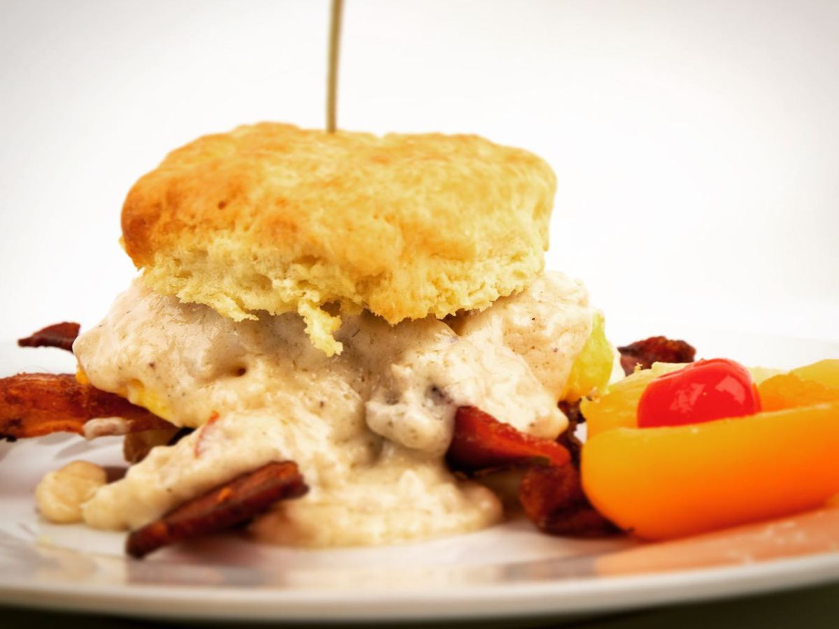 Biscuit breakfast sandwich with fruit surrounding it.