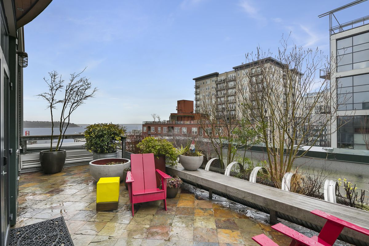A larger, tiled terrace, also with a water view. A long planter stretches to the right, and two red chairs are set up.