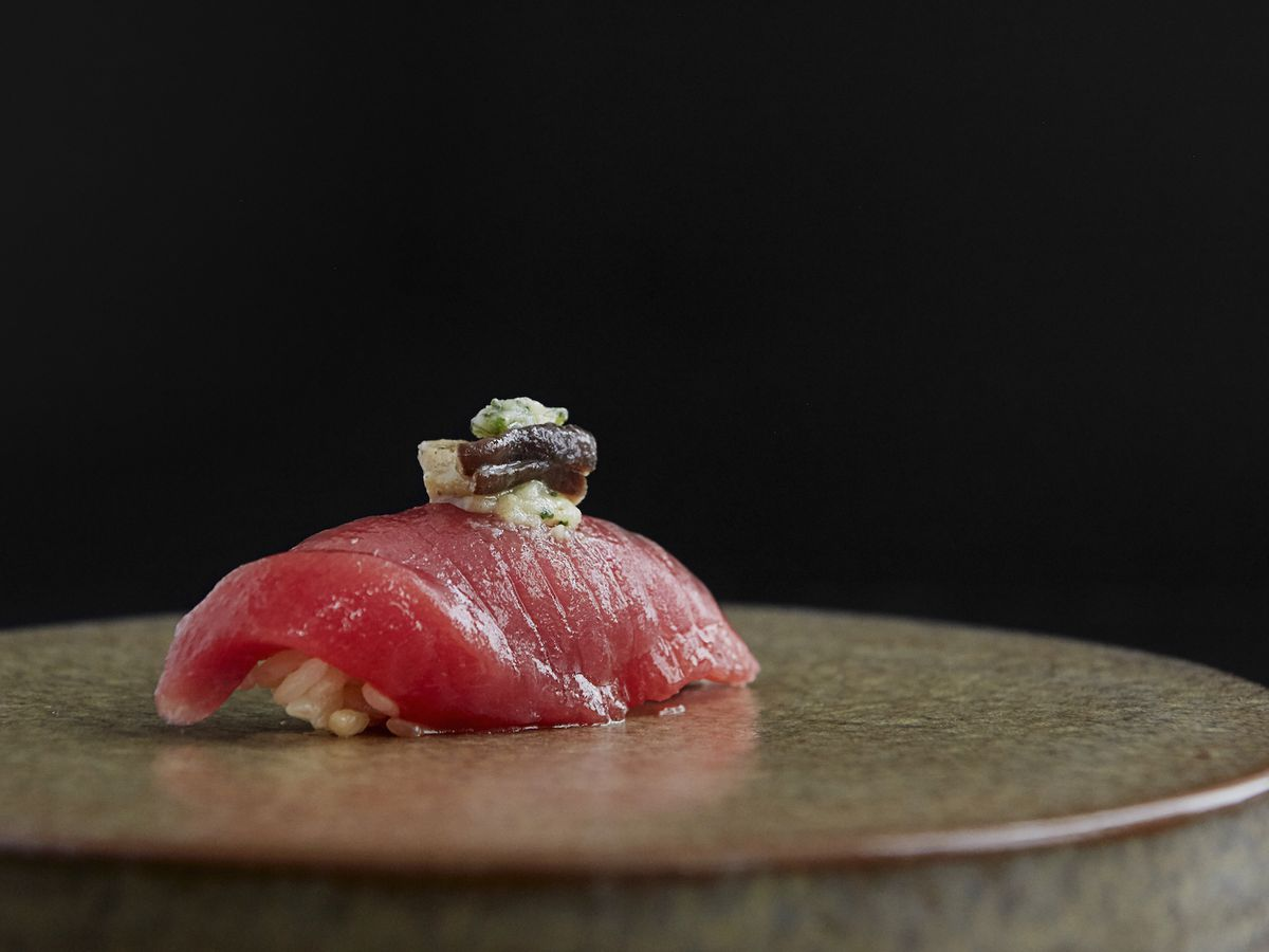 A piece of pink fish topped with ginger and a black paste