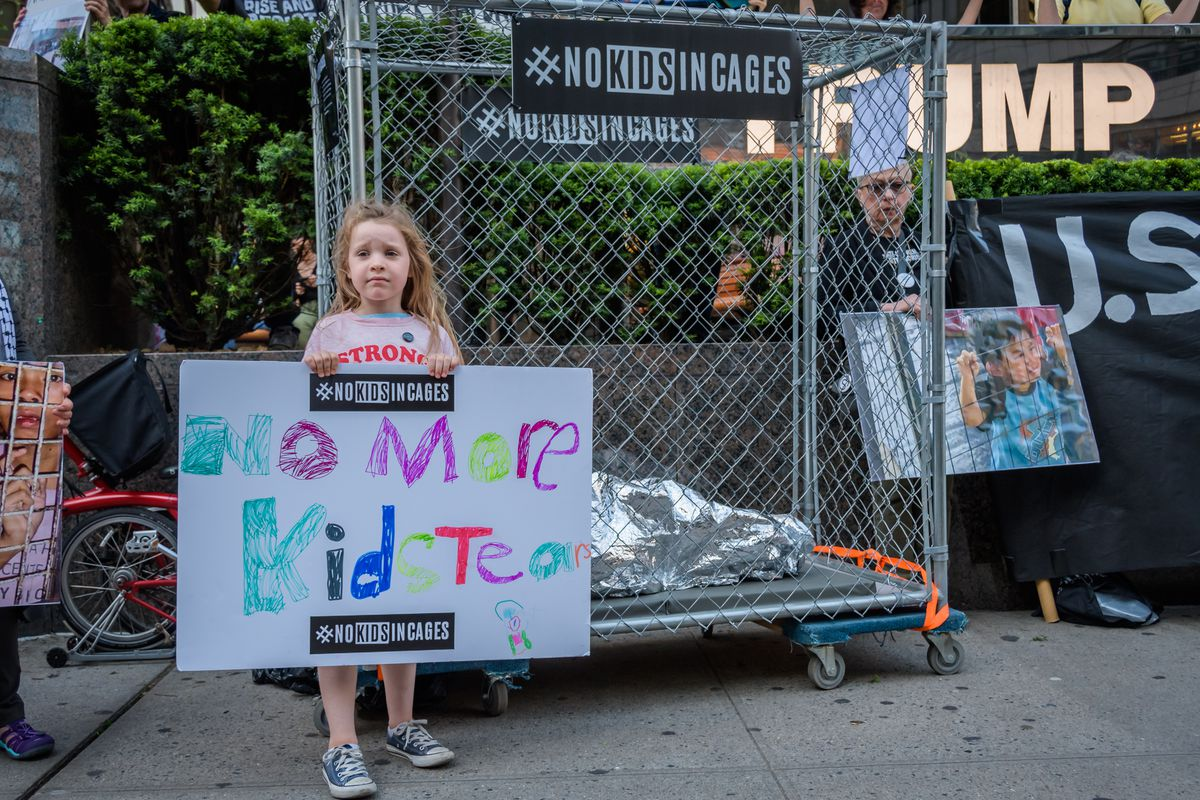 """A girl holding up a sign stating """"No more kid tears""""  stands in front of a dummy of a child huddled under a mylar blanket in a chain-link cage."""