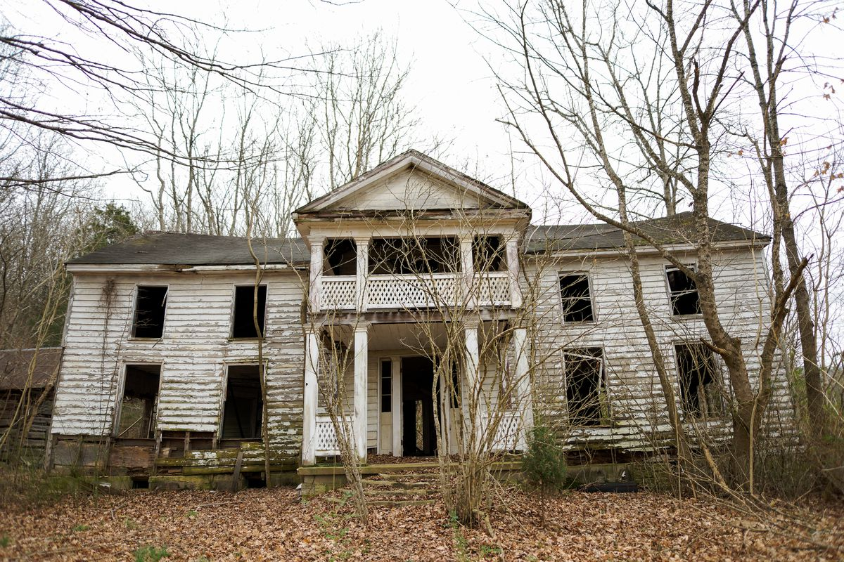 A dilapidated colonial-style white house in the colonial style sits in a woodland setting with lots of dead trees.
