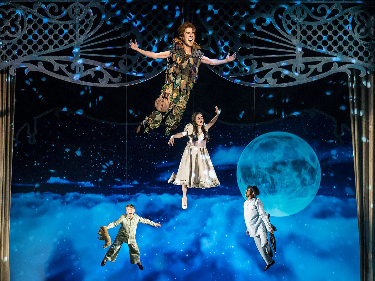 """Peter Pan (Johnny Shea) leads the Darling siblings (Carter Graf, Elizabeth Stenholt, and Cameron Goode) on a high-flying adventure to Neverland in """"Peter Pan — A Musical Adventure,"""" streaming free on-demand for the holiday season from Chicago Shakespeare Theater."""